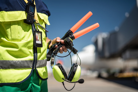 Foto de Waiting for plane. Close up of airport worker torso in vest and arm with headset. Airdrome on blurred background - Imagen libre de derechos