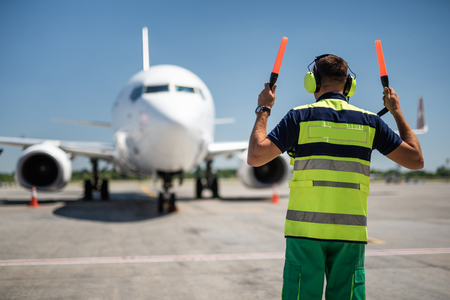 Foto per Welcome home. Back view of aviation marshaller directing aircraft landing - Immagine Royalty Free