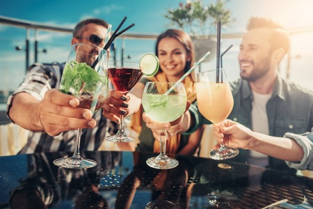 Photo for Drink for you. Close up of various cocktails in people hands. Company sitting at the table of outdoor bar - Royalty Free Image