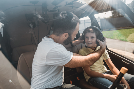 Foto de Happy male pilot putting headset on cheerful kid. They locating inside of rotorcraft during communication - Imagen libre de derechos