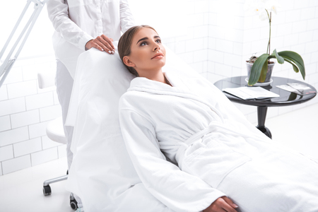 Photo for Enjoying spa. Positive young woman waiting for wellness procedure. Cropped cosmetic specialist standing behind deck chair - Royalty Free Image