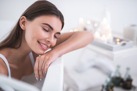 Photo for Portrait of satisfied woman with closing eyes resting during cosmetic procedure in bath opposite shelf with candles. She closing eyes during pleasure - Royalty Free Image