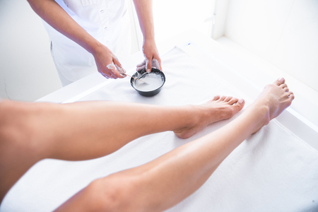 Foto de Preparation for therapy. Close up of female legs on massage table and beautician hands. Arms holding bowl with cosmetic mixture - Imagen libre de derechos