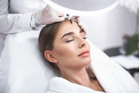 Photo pour Enjoying the procedure. Close up portrait of smiling young lady with closed eyes. She is getting facial skin lifting treatment at beauty salon - image libre de droit
