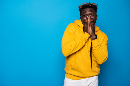 Photo for Feeling a little shy. Waist up portrait of young man in yellow hoodie covering nose and lips with arms. Isolated on blue background - Royalty Free Image