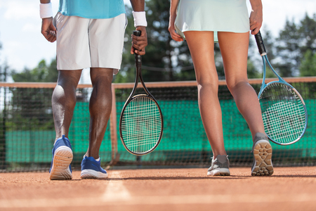 Foto de Close up of male and female sports people legs while playing active game. They are standing on court with focus on back and holding rackets. Team mates are preparing for match - Imagen libre de derechos