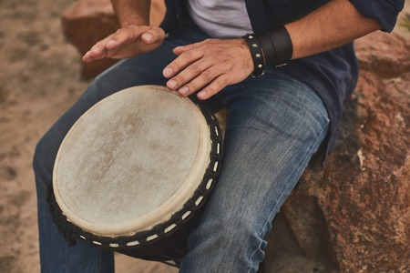 Photo for Music improvisation. Close up of male hands playing music using djembe - Royalty Free Image