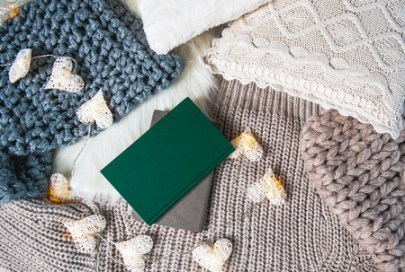 Photo for Top view two copybooks and fairy lights situating on knitted clothes. Comfort concept - Royalty Free Image