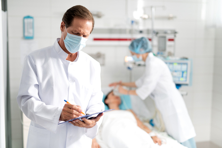 Photo pour Waist up portrait of male doctor in protective mask writing down information about condition of young lady on clipboard. Female assistant doing artificial inhalation on blurred background - image libre de droit