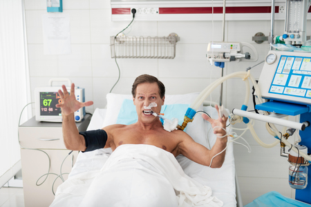 Foto de Portrait of enraged patient on mechanical ventilator lying in bed and looking at camera with grimace on his face. He is raising hands and screaming with madness - Imagen libre de derechos