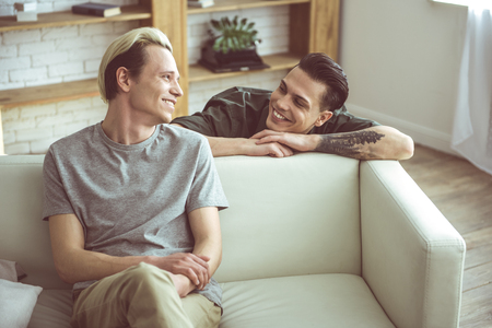 Photo pour Are you flirting with me. Toned portrait of blond young man sitting on couch while his cheerful boyfriend standing behind and gazing at him - image libre de droit