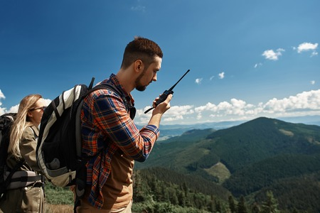 Foto de Couple is backpacking in mountains together. They are standing while guy is speaking via walkie-talkie - Imagen libre de derechos