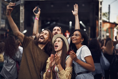 Foto de Having fun. Waist up portrait of young people taking photo with smartphone while enjoying concert - Imagen libre de derechos