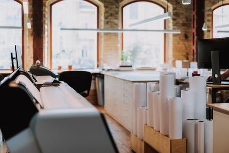 Foto de Paper rolls standing on the floor of typography with modern equipment - Imagen libre de derechos
