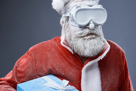 Photo for Studio portrait of bearded old man in Santa costume covered with snow. He is holding blue gift box with ribbon - Royalty Free Image