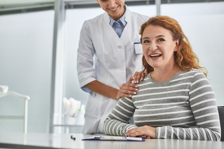 Foto de Portrait of beautiful middle-aged lady looking at camera with smile. Cropped young gynecologist touching her shoulder - Imagen libre de derechos