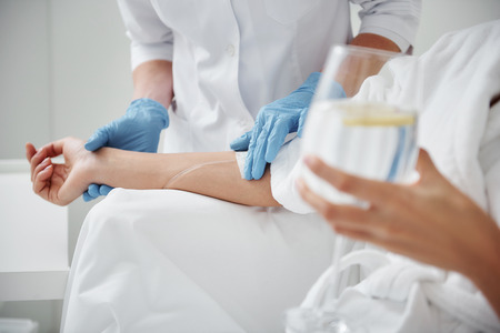 Foto de Close up of physician hand in sterile glove checking tube and needle for IV infusion on woman arm. Girl holding glass with lemon water - Imagen libre de derechos