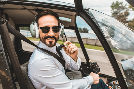 Foto de Positive enthusiastic young pilot sitting in the helicopter cabin and smiling while touching the headphones - Imagen libre de derechos