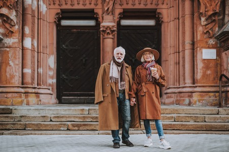 Photo pour Full length portrait of stylish bearded man and his wife standing near old building. Lady in hat holding cup of coffee - image libre de droit
