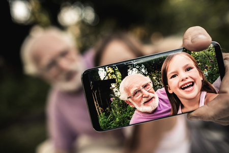 Photo pour Senior gray-haired man in glasses with funny laughing girl shooting themselves on smartphone while sitting in summer garden. Focus on phone screen - image libre de droit