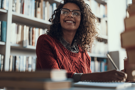 Photo pour Positive emotional curly student in warm sweater holding a pencil and smiling while sitting in the library and looking into the distance - image libre de droit