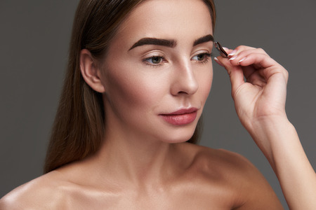 Photo pour Close up portrait of charming woman with naked shoulders correcting eyebrow form. Isolated on gray background - image libre de droit