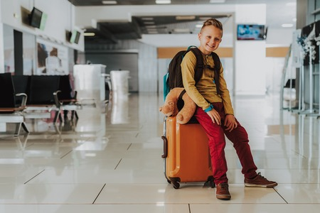 Photo for Full length portrait of merry boy sitting on suitcase in lobby. - Royalty Free Image