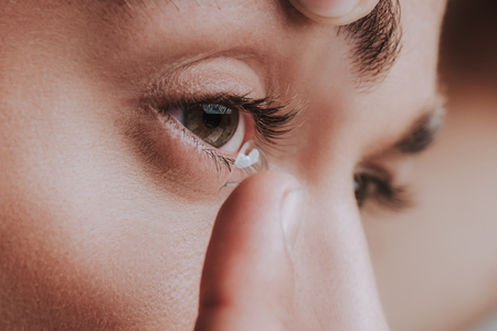 Photo for Close up of the eye and person placing contact lens on the surface of it - Royalty Free Image