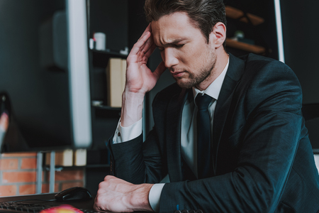 Foto de Unbearable headache. Close up of young man in elegant suit sitting at the table with his eyes closed and touching head while having sudden pain - Imagen libre de derechos