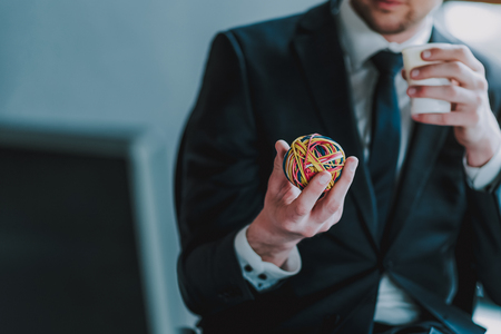 Photo pour Close up of man in elegant suit sitting with a carton cup in left hand. He holding ball of colorful rubber bands in right hand - image libre de droit