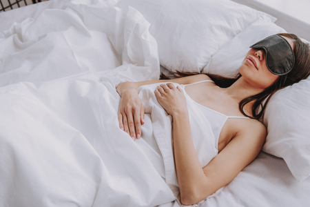 Photo for High angle of happy young lady with sleep mask covering up with soft blanket while lying in bedroom at home. Concept of rest - Royalty Free Image