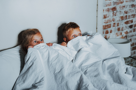 Photo for Horror movie. Waist up of scared little brother and sister hiding under white blanket while watching terrible movie on television at home - Royalty Free Image