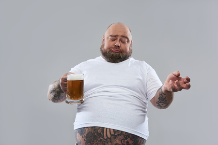Foto de Waist up of fat lazy man closing his eyes while being drunk and holding a glass of beer while being isolated on the grey background - Imagen libre de derechos
