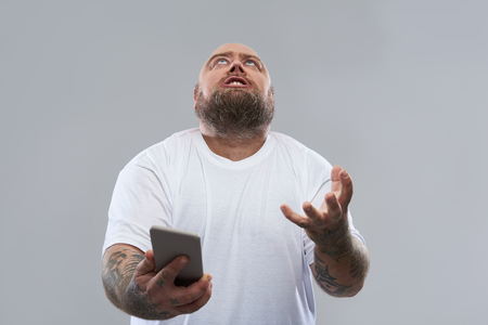 Foto de Bearded fat tattooed man in white T-shirt standing isolated on the grey background and putting his head and hand up - Imagen libre de derechos