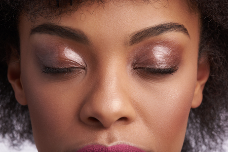 Foto de Fashion make up and natural look. Close up upper face portrait of sensual calm afro american woman with nude shimmery eyeshadow on closing eyes - Imagen libre de derechos