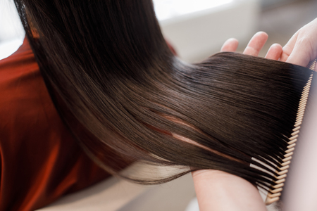 Foto de Close up. of beautiful silky hair is in hands of stylist while she combing by hairbrush - Imagen libre de derechos