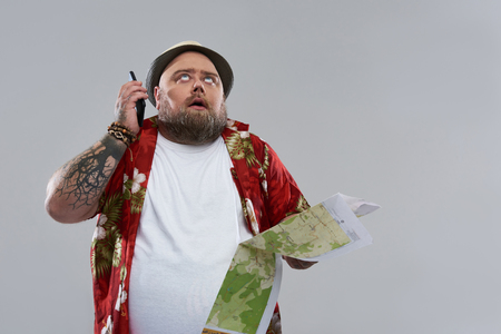Foto de Unbearable phone talk. Tired fat bearded traveler in Hawaiian shirt looking at the sky and putting smartphone from his ear while standing isolated on the grey background with map in his hand - Imagen libre de derechos