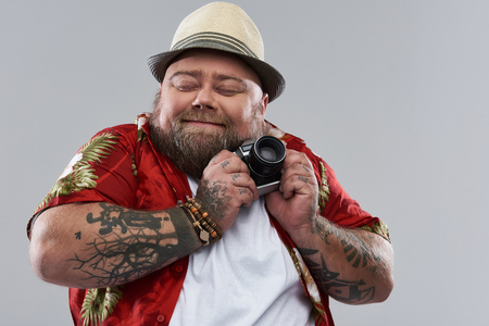 Photo pour Favorite camera. Pretty funny bearded tourist in Hawaiian shirt smiling and closing his eyes while standing alone isolated on the grey background and gently pressing his retro camera to the chest - image libre de droit