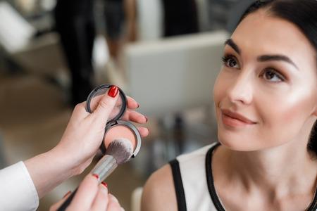 Foto de Close up of makeup artist emphasizing cheekbones while using peach blush in beauty salon - Imagen libre de derechos