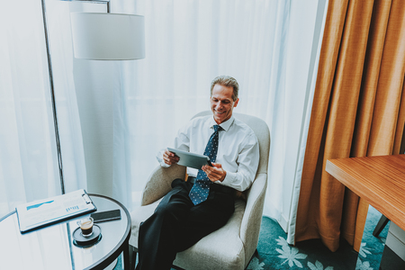 Photo pour Businessman with tablet. Happy enthusiastic businessman looking glad while sitting in the armchair with coffee table in front of him and using a modern tablet - image libre de droit