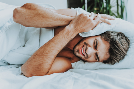 Foto de It is awful noise. Close up of young despairing man laying in bed and pressing pillow to his head while disturbing by too loud noise - Imagen libre de derechos