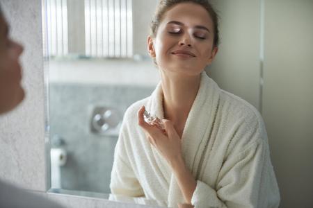 Foto de Young smiling lady enjoying her perfume in morning - Imagen libre de derechos