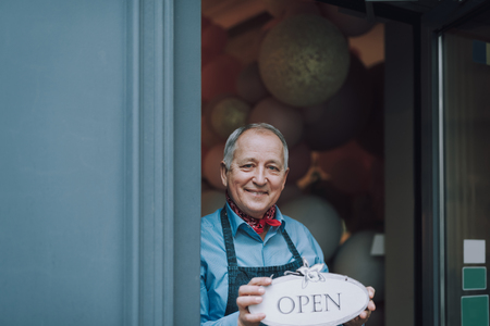 Foto de Joyful old man standing in the doorway of cafe and holding open sign - Imagen libre de derechos