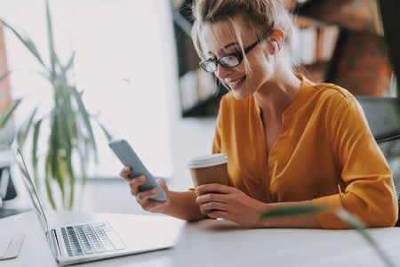 Photo for Woman with smartphone sitting in front of the laptop - Royalty Free Image