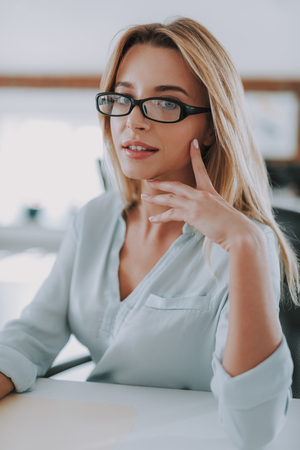 Foto de Portrait of the fair haired woman wearing glasses sitting at the table - Imagen libre de derechos