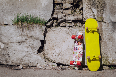 Photo pour Two colorful skateboard leaning on cracked wall - image libre de droit