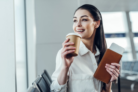 Photo for Delighted young woman is expecting flight with hot drink - Royalty Free Image