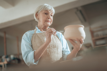 Photo for Low angle of old craftswoman painting her pot in workshop - Royalty Free Image