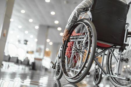 Foto de Elderly lady is using a wheelchair in airport - Imagen libre de derechos