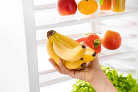 Foto de Young lady hand taking bananas from refrigerator - Imagen libre de derechos